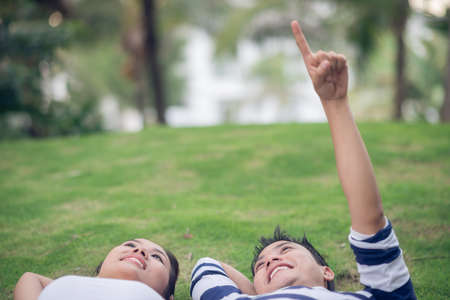 Close-up of a young couple lying on the grass where a guy showing at something
