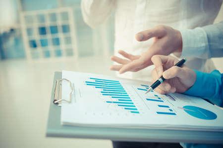 Closeup immagine di un consulente aziendale spiegando gli aspetti finanziari al collega in primo piano