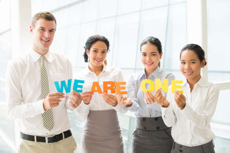 Copy-spaced portrait of a business international team holding colorful letters and looking at camera