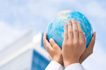 Imagen recortada de los líderes de la empresa que sostiene una miniatura de globo en manos en el signo de la unidad Foto de archivo