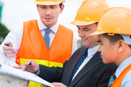 Engineers looking at the plan of the building
