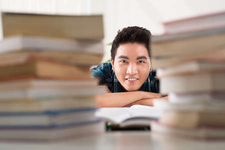 stack of paper: Portrait of a young student among stacks of books preparing for the exams on the foreground Stock Photo