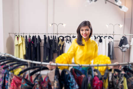 customer tailor: Portrait of a young attractive lady doing the shopping in the fashionable boutique on the foreground Stock Photo