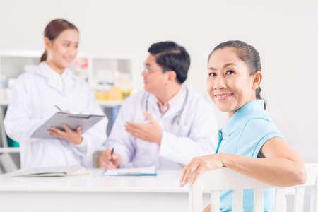 クリニックで座っている年配の女性