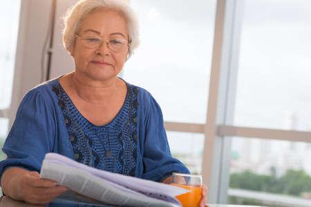 Mature Asian woman reading newspaper
