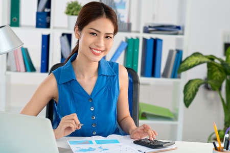 Young Vietnamese accountant working with the documents