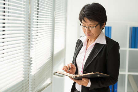 Japanese businesswoman checking schedule in her notebook