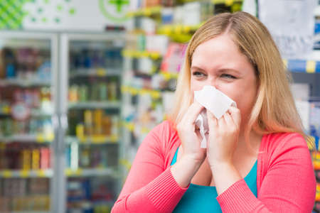 running nose: Copy-spaced image of a sneezing young woman having flue being in chemists Stock Photo