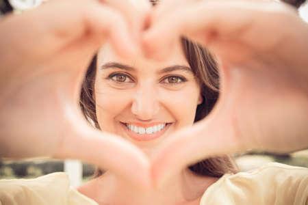 Porträt einer reizenden Frau, die Herz von den Fingern macht