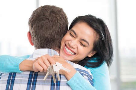 key: Young woman with keys in hand embracing her husband Stock Photo