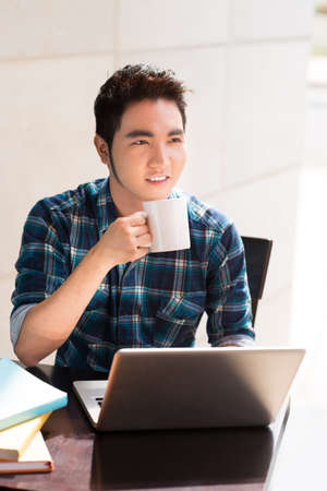 Vertical image of a guy drinking coffee at the Internet cafe