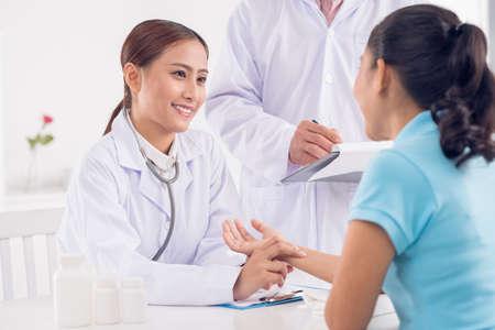 Jonge arts die de bloeddruk van de vrouw controleert