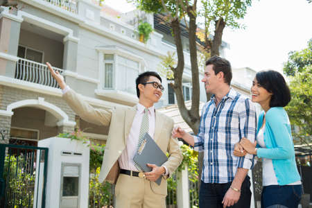 Estate agent showing a house to the young family 版權商用圖片