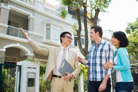 L'agent immobilier montrant une maison à la jeune famille Banque d'images - 70421485