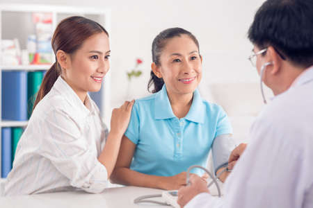 Woman visiting doctor with her mother Stock Photo