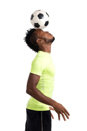 Soccer player holding a ball on his head Stock Photo