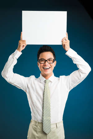 Laughing businessman holding empty board over his head Stock Photo