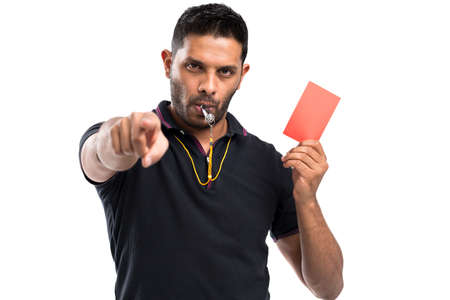 Referee whistling and holding a red card Stock Photo