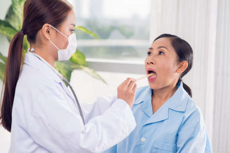 depressor: Young doctor checking mouth of her patient