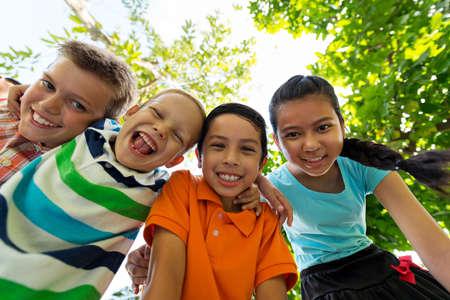 niños felices: Cuatro niños abrazados y sonriendo, vista desde abajo Foto de archivo