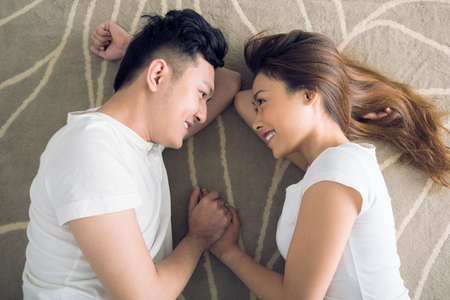 Smiling young couple holding hands and looking at each other Stock Photo