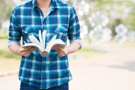 Cropped image of a student with an open book in hands