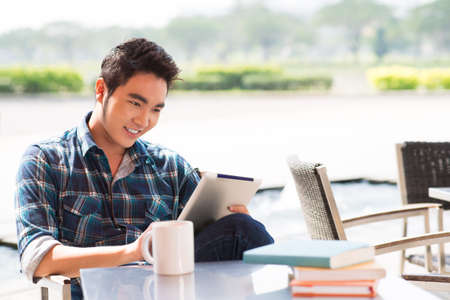 Copy-spaced image of a cheerful guy networking at a cafe Stock Photo
