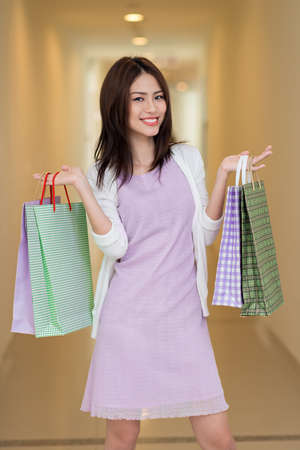 Smiling Vietnamese woman with shopping bags Stock Photo