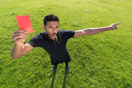 Referee whistling and showing red card Stock Photo