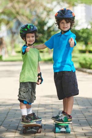 skateboarder: Cheerful little boys skateboarding in park
