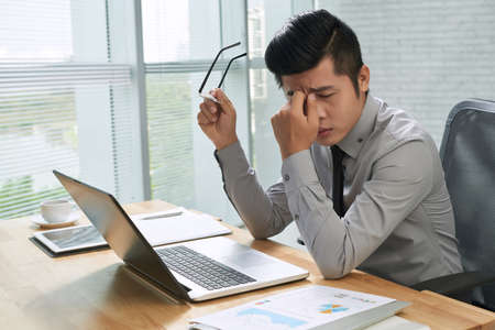 Exhausted businessman working on laptop Imagens