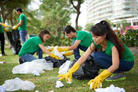 공원 잔디에서 쓰레기를 모으고 있습니다.