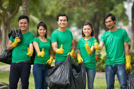 Asian friends with full bin bags