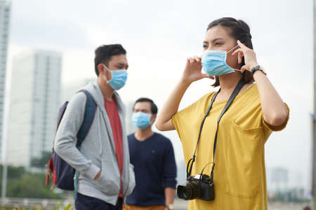 Asian woman putting on protective mask Stock Photo