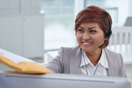Pretty smiling call center operator receiving package