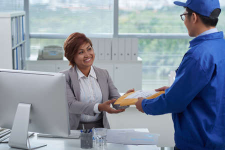 Delivery man giving package to smiling business woman Stock Photo