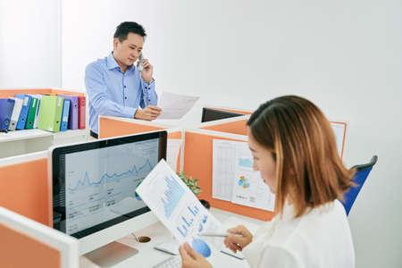 singaporean: Entrepreneur reading business document when talking on phone Stock Photo