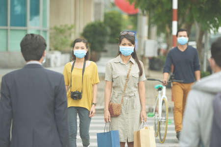personas en la calle: Asian people in the street wearing protective masks