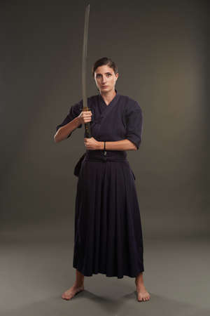 Full-length portrait of woman with samurai sword