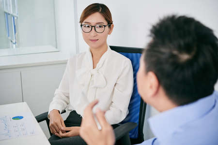 Pretty Korean business lady conducting interview with businessman