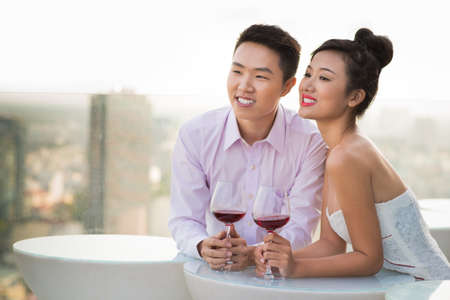 Close-up image of a young couple standing at a cafe and dreaming about their future