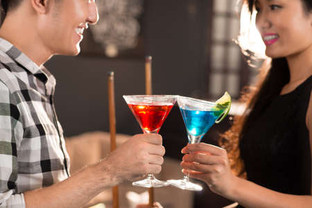 Asian couple clinking their glasses in the bar Stock Photo