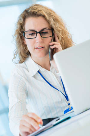 Closeup image of a businesswoman on the phone while making notes on the foreground Stock Photo
