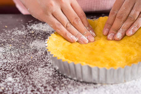 Close-up of female hands preparing tasty cake on the foreground Stock Photo