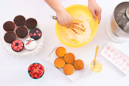 silicio: Below view of a table where human hands whisking dough for cake with a silicone beater, prepared fancy cakes and raspberry are nearby
