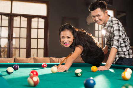 Young Vietnamese couple playing pool in the bar
