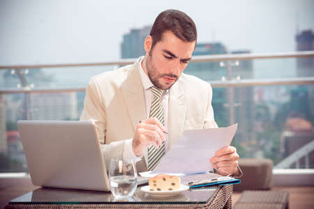 Image of a serious handsome businessman at work at a cafe