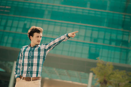 Handsome young man standing outside and pointing on something Stock Photo