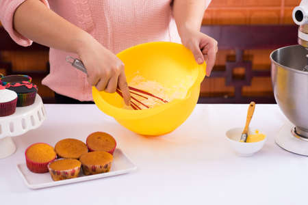 Close-up of female hands beating dough in the kitchen equipment on the foreground