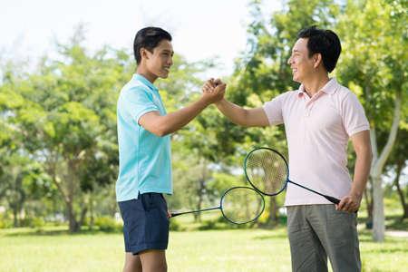 Afbeelding met een kopie op afstand van een zoon en een vader met een vriendelijke badmintonwedstrijd en handshaking in het teken van vriendschap Stockfoto